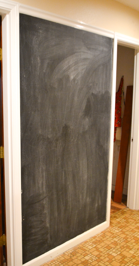 A wall between doorways is painted with black chalkboard paint