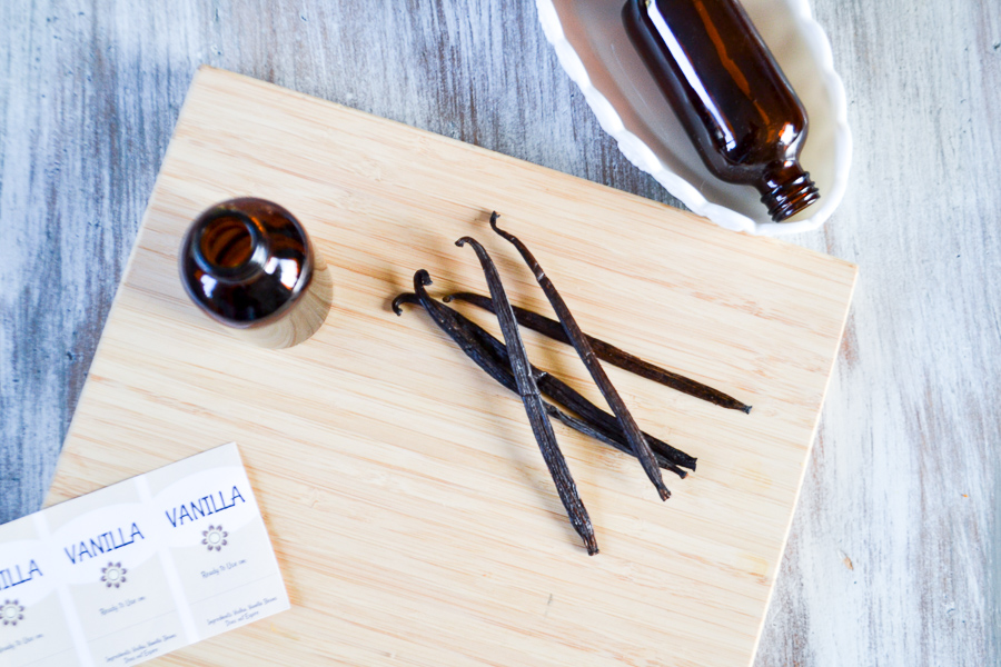 An above view of 5 vanilla beans randomly sitting on a cutting board with an amber glass bottle sitting next to them and a bottle on it's side in a white dish with a vanilla label in the corner of the picture