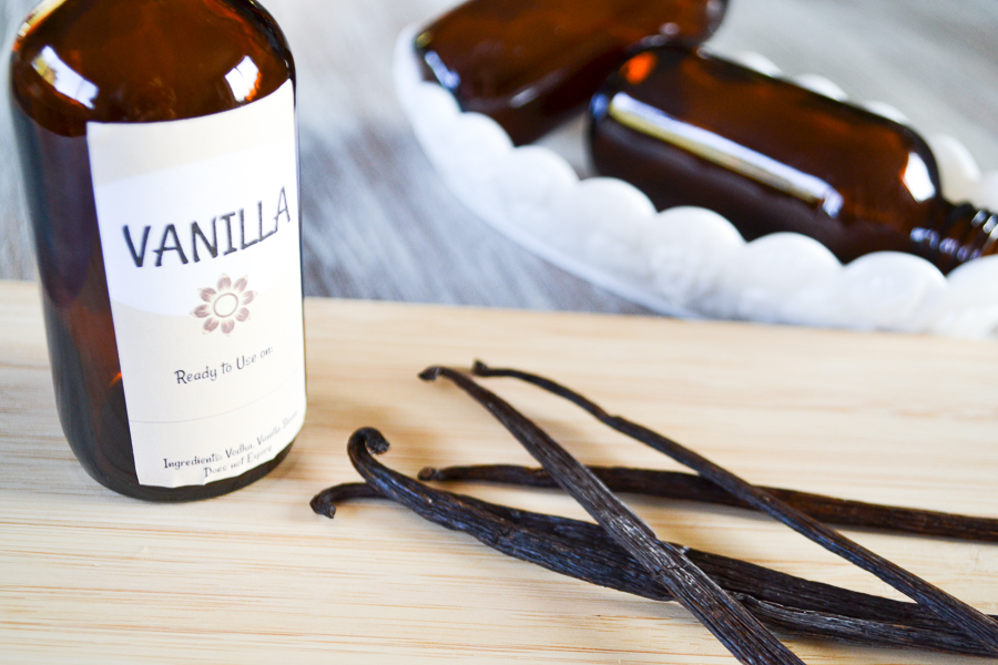 A close up view of a glass amber bottle with a vanilla label behind vanilla beans with two bottles on their side in the background