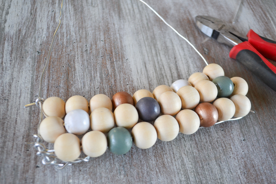 A close up photo of three rows of random wood beads on a wire triangle frame
