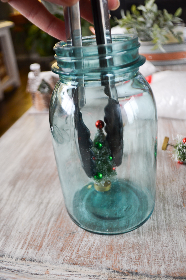 A vintage blue mason jar with a pair of black kitchen tongs holding a bottle tree with ornaments on it placing this into the jar