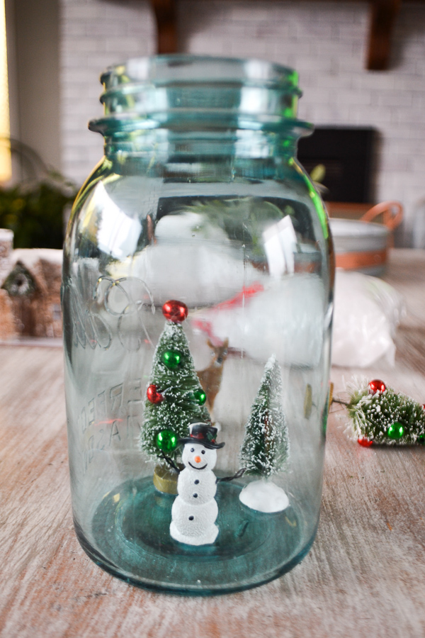 A blue mason jar sitting o a table with two bottle trees and a snowman stuck to the bottom