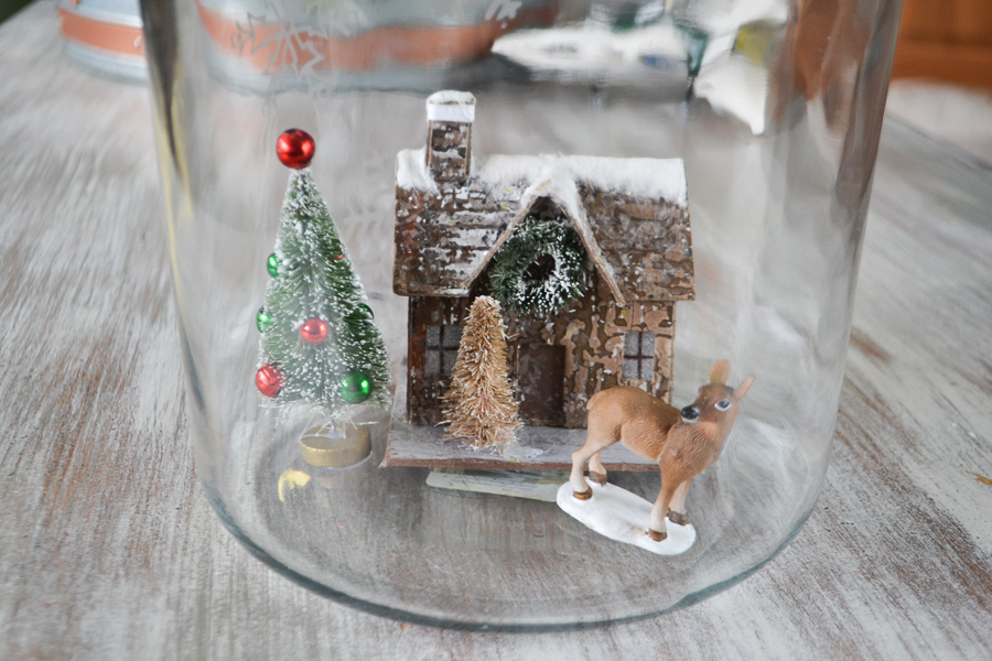 A clear glass container with a brown cabin and bottle tree and deer in the front