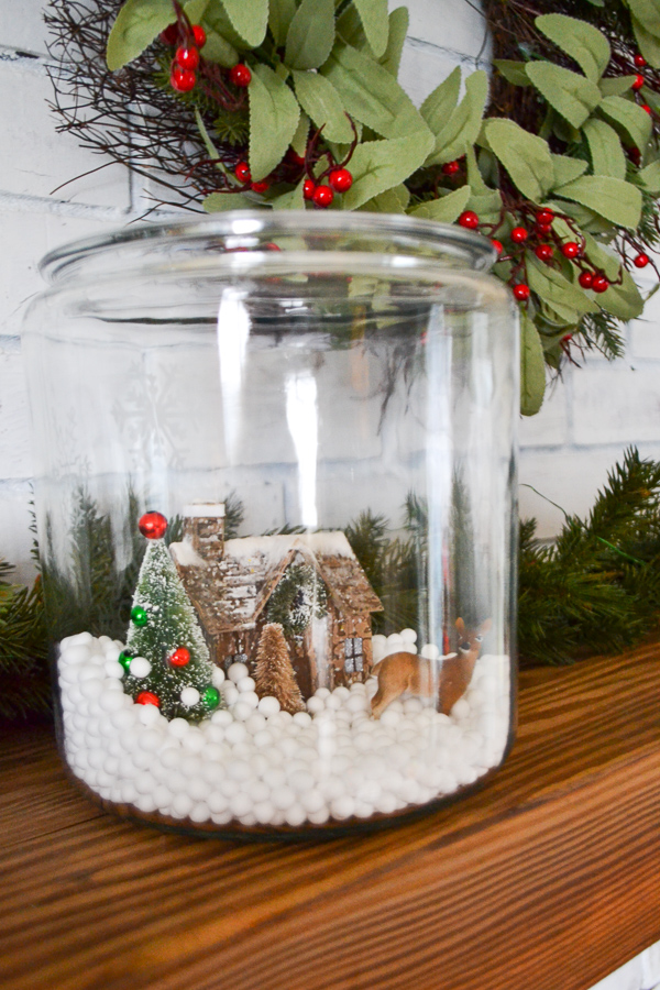 A clear glass container sitting on a wood mantle with garland in the background with snow, a cabin, tree and deer inside the snow globe