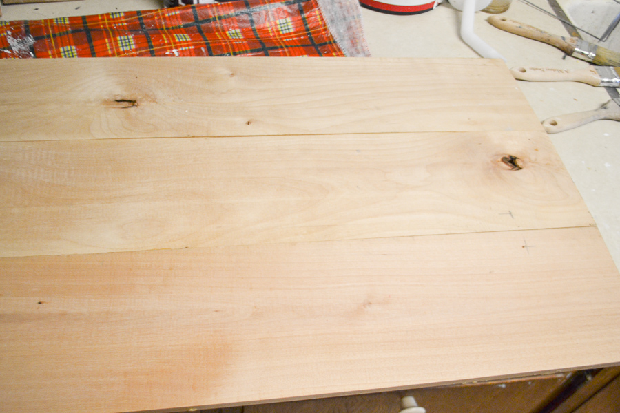 Three pieces of wood glued together and sitting on a counter ready for paint