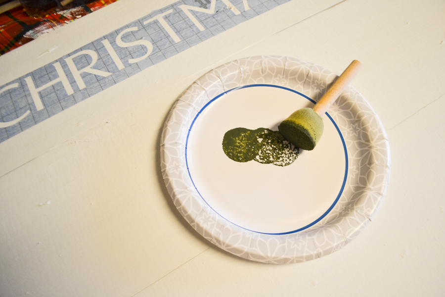A paper plate sitting on a white board with a sponge painter on the plate