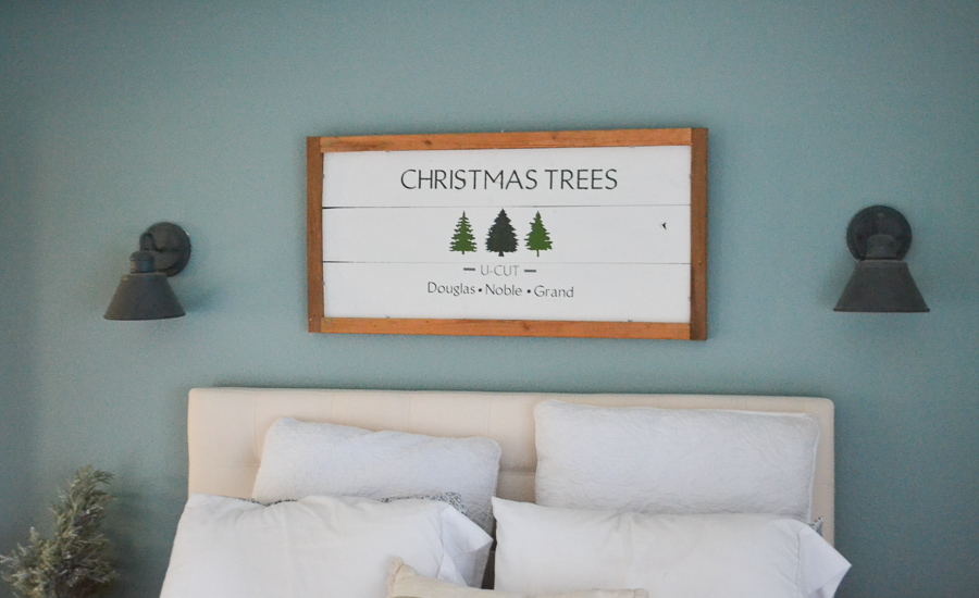 A close up of a white painted Christmas tree sign with an unfinished wood frame