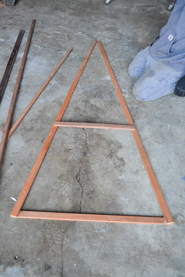 A wood trim triangle laying on a concrete floor with a piece of wood in the middle as a brace