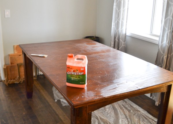 A dark stained table with a jug of orange Citri-strip sitting on it with plastic sheeting under the table
