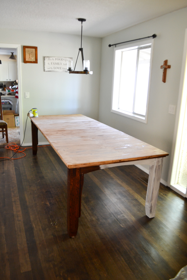A far off shot of a large dining room table with the top tha thas been refinished and sanded with dark wood floors and dark table legs
