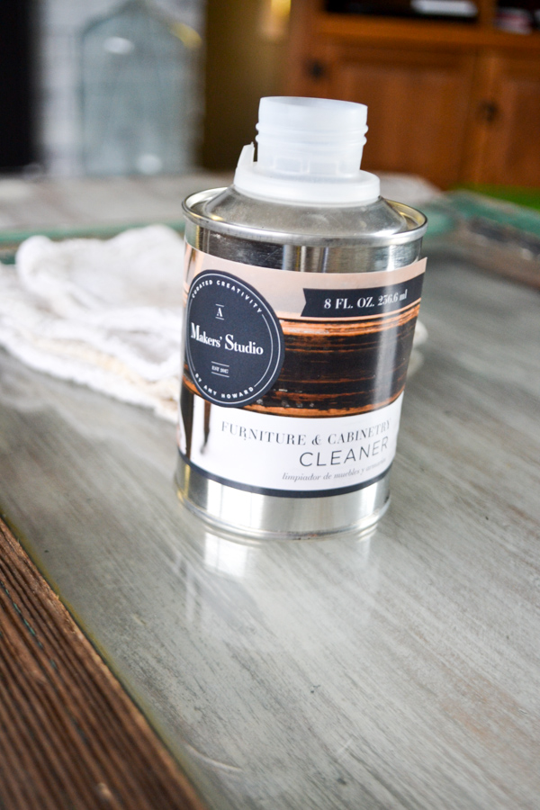 A silver can of furniture cleaner sitting on a glass window frame with a white rag laying behind the cleaner