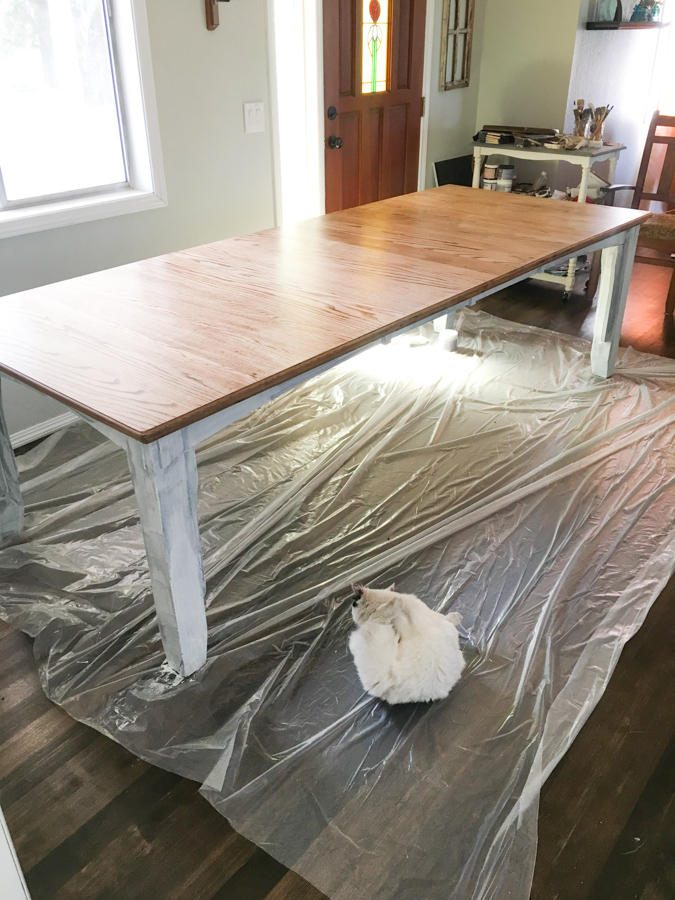 A wide shot of a long dining room table with a refinished top and white painted legs with plastic sheeting laying underneath