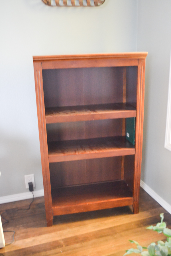 An empty dark wood bookcase sitting in the corner of a living room