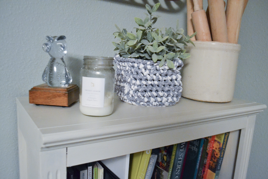 A close up of the the top of a bookcase with a candle, crock filled with rolling pins and faux green flower