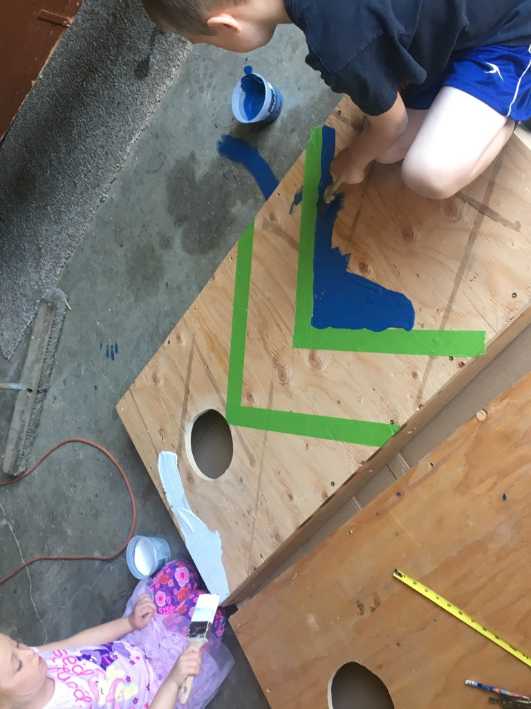 Two children using white and blue paint to paint a plywood cornhole game board set
