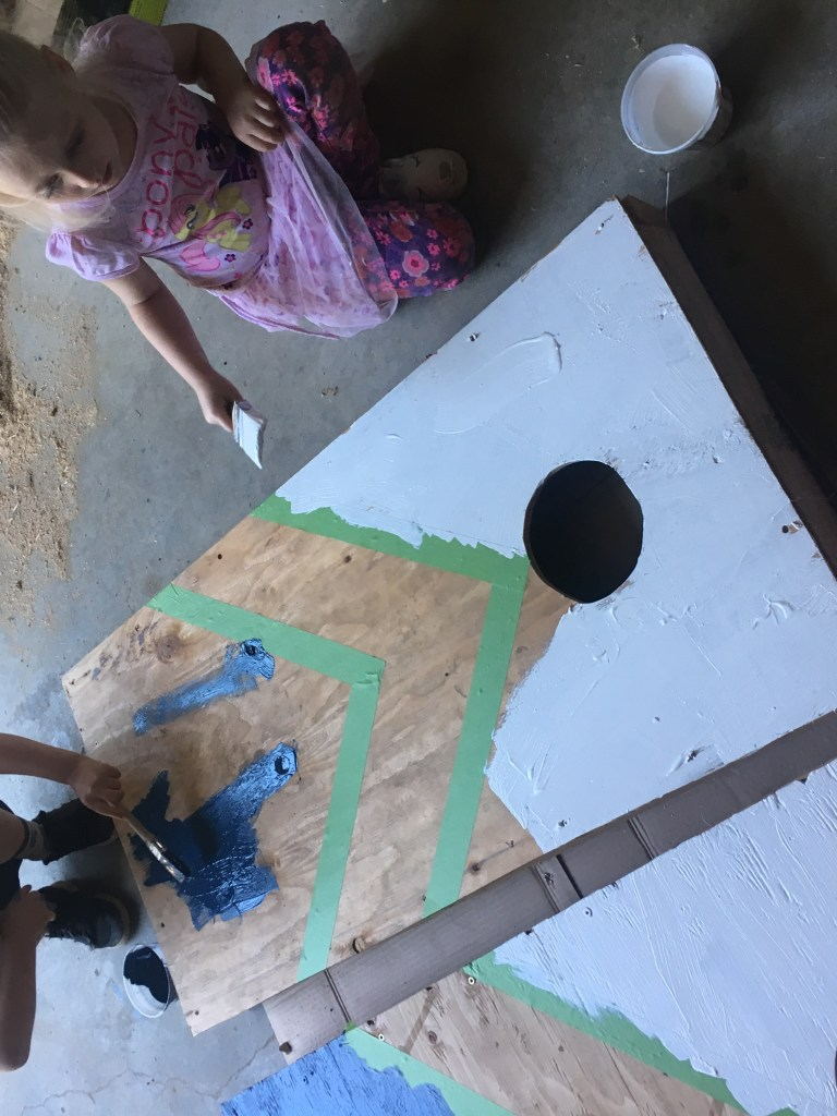 Two plywood cornhole boards being painted by two children on a concrete floor