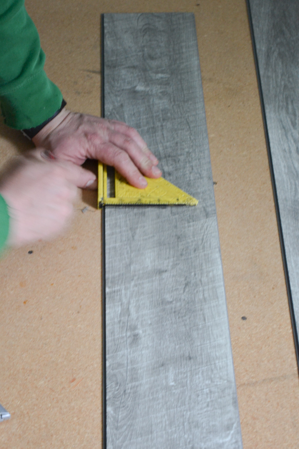 A close up of a gray vinyl flooing plank with a man's hand using a straight edge to measure a cut spot