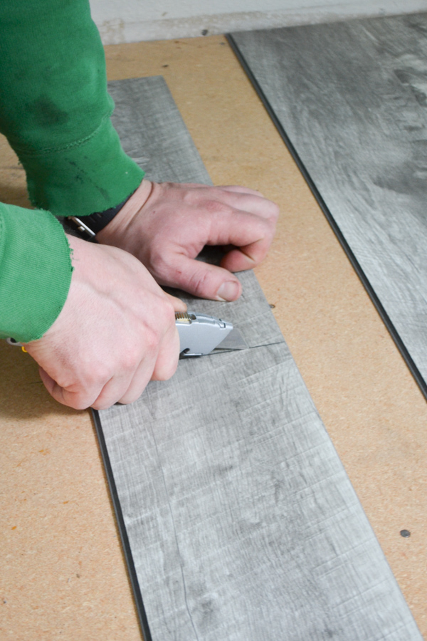 A close up of a man's hand holding a box cutter and actively cuts a gray vinyl plank on a subfloor