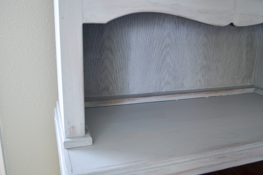 A close up of a hutch with one coat of milk paint in a gray blue