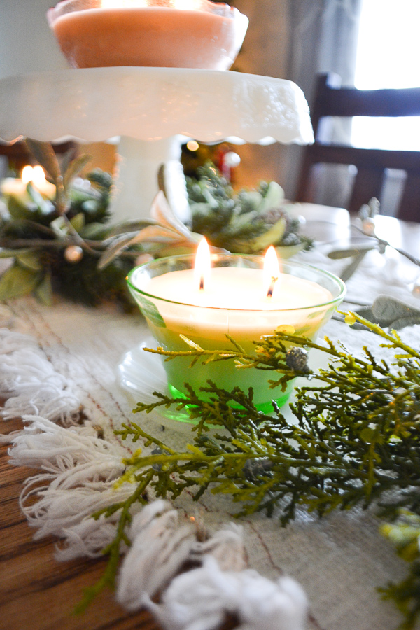 A close up of a green depression glass soy candle with two wicks lit on a Christmas table decor