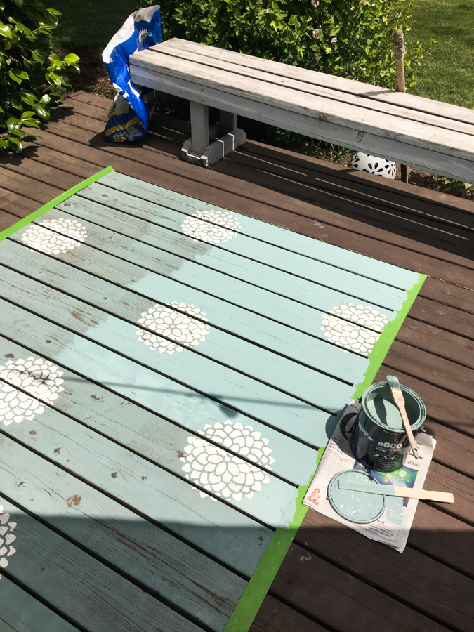 A far off picture of a deck rug being repainted with a new coat of fresh aqua colored paint