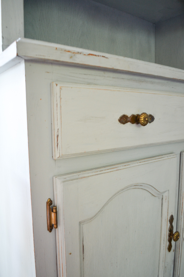 A close up of a hutch drawer with light distressing