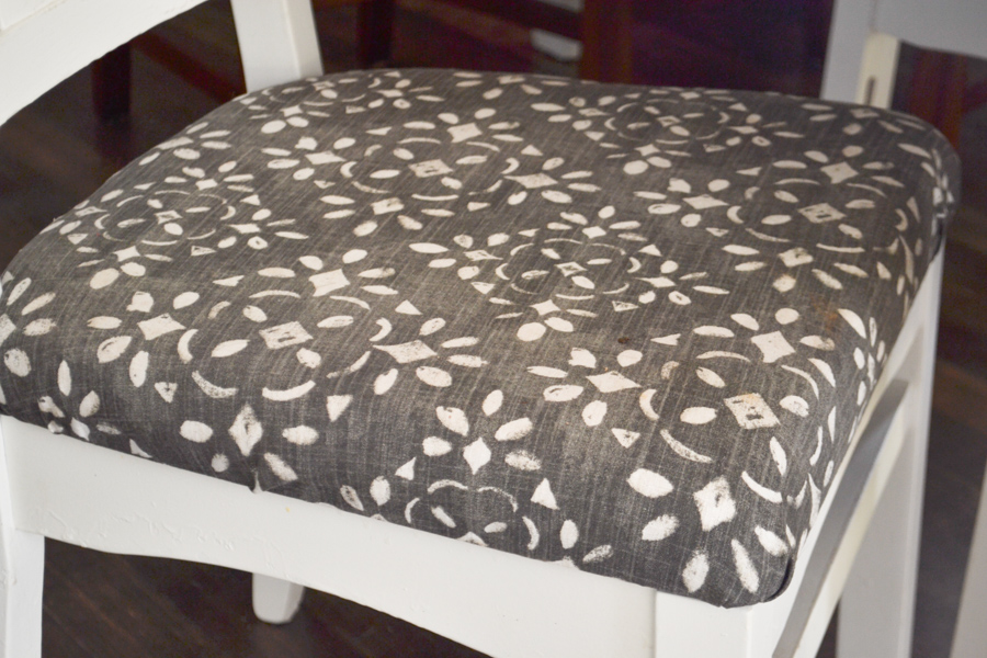 A close up of a blue and white fabric seat on a white chair