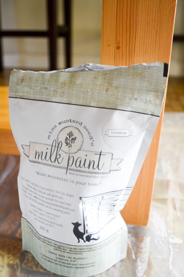 A close up of a bag of powdered Miss Mustard Seed Milk Paint sitting in front of a maple colored wood table leg