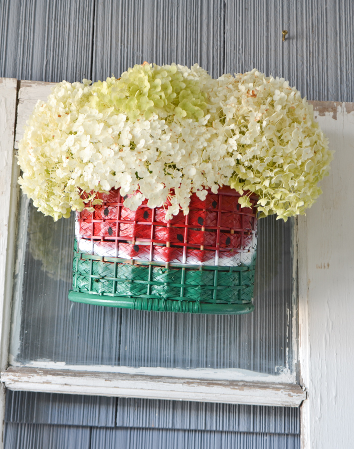 A watermelon painted basket with white hydrangeas inside hanging on an old white door