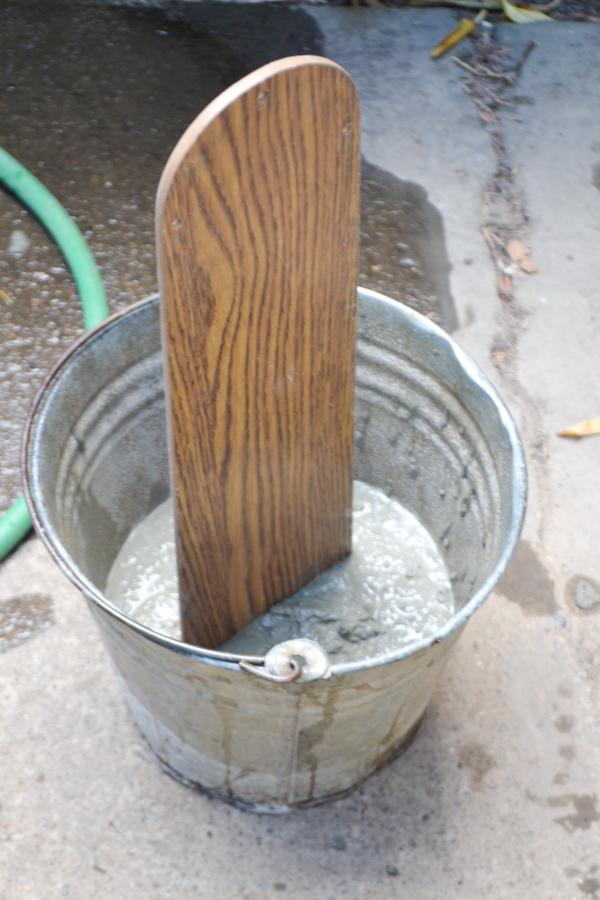An old fan blade sunk in concrete in a metal bucket