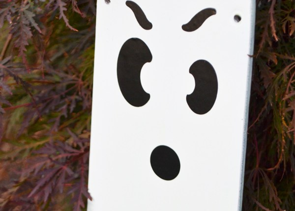 A close up of a rounded fan blade painted white with a black ghost face against a red bush