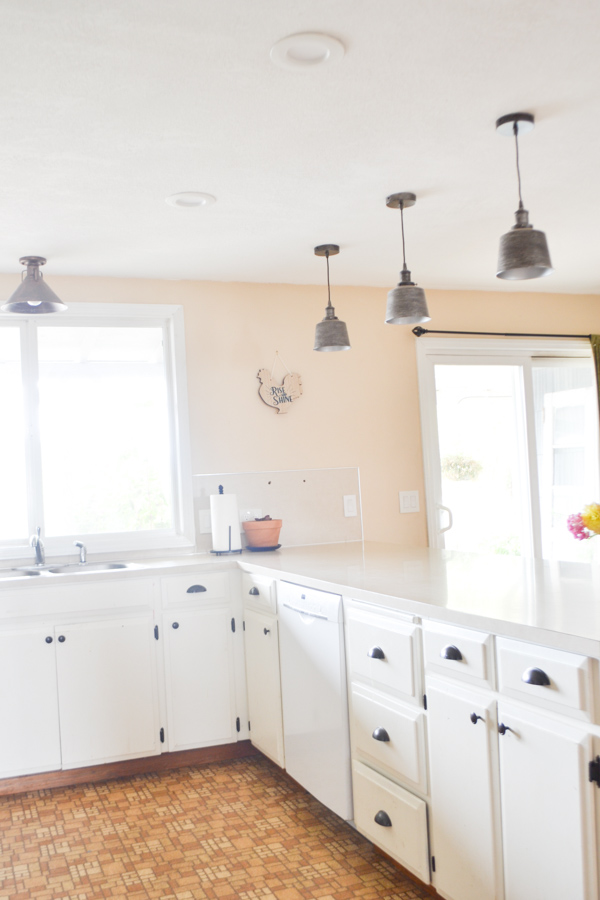 A view of a U shaped kitchen into the corner with an island and a window above the sink to the left and a sliding door to the right