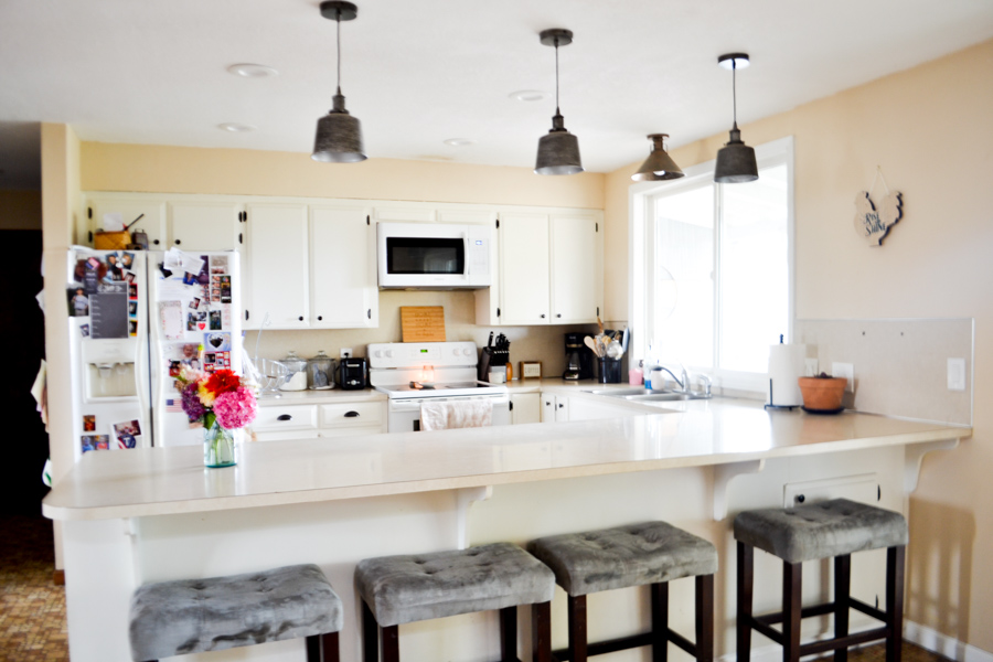 A side view of a kitchen with silver pendant lights hanging above the bar area and a pink flower bouquet on the counter