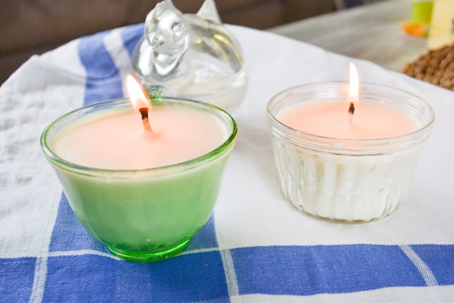 A close up of two burning soy candles in a green depression glass teacup and a clear glass jelly jar