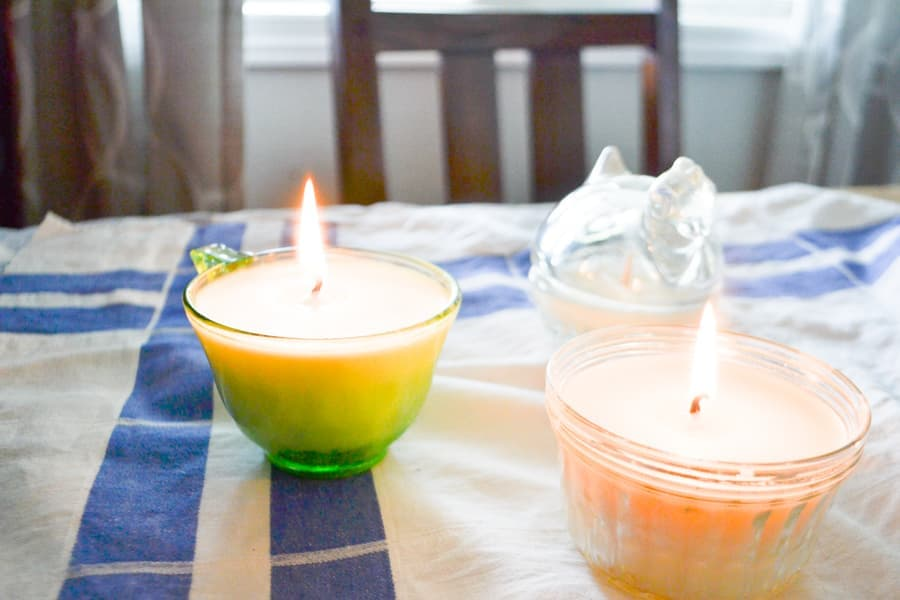two glass candles siting on a blue and white tablecloth