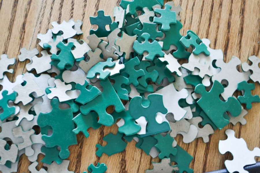 A pile of green painted puzzle pieces laying on a light colored table