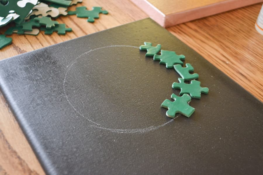 A close up of a black painted canvas with green puzzle pieces glued to part of a white traced circle