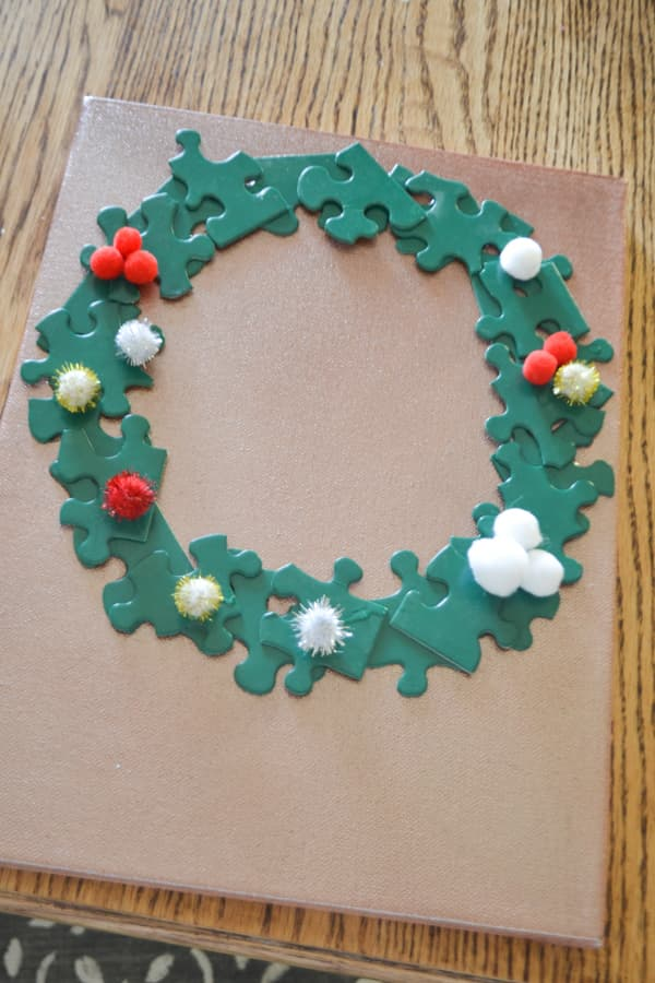 A copper painted canvas on a table with a green puzzle piece wreath with red, gold and silver pom poms glued on