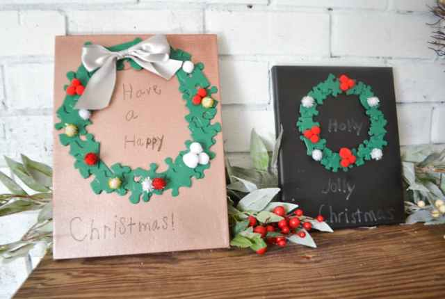 Two art canvases sitting next to each other, one black, one copper with green puzzle piece wreaths, one with the words holly jolly Christmas and the that says Have a Happy Christmas