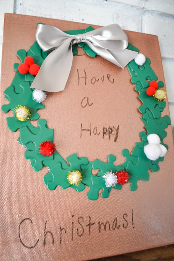 A close up of a copper painted art canvas with a green puzzle piece wreath with pom poms and a silver bow with the words Have a Happy Christmas written in a childs handwriting