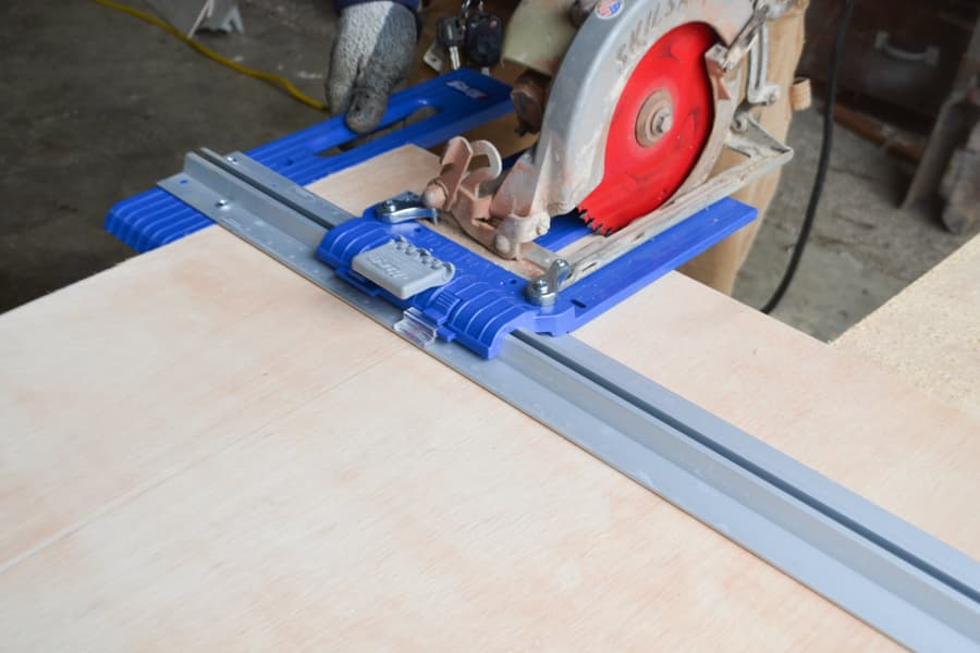 A circular saw attached to a Kreg jig lined up on a piece of plywood