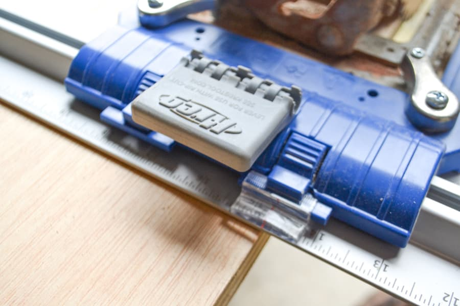 A close up picture of a Kreg Jig placed against a piece of plywood
