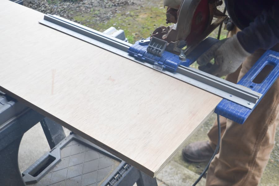 A plywood sheet on saw horses with a Kreg rip cut jig with a circular saw attached using to cut the plywood