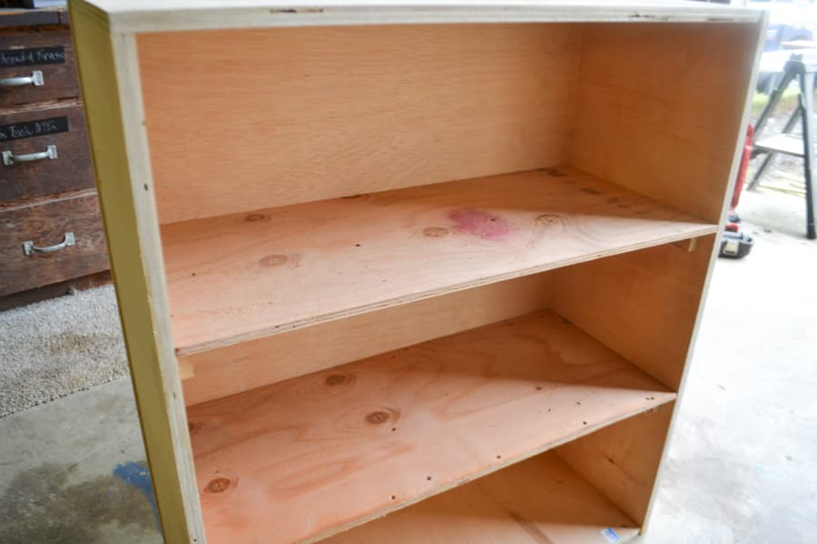 A close up of a two shelf unit made out of plywood, unpainted