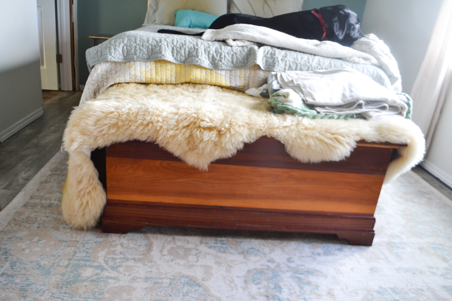 A brown hope chest sitting at the end of a bed with a sheepskin rug on top and a rug underneath