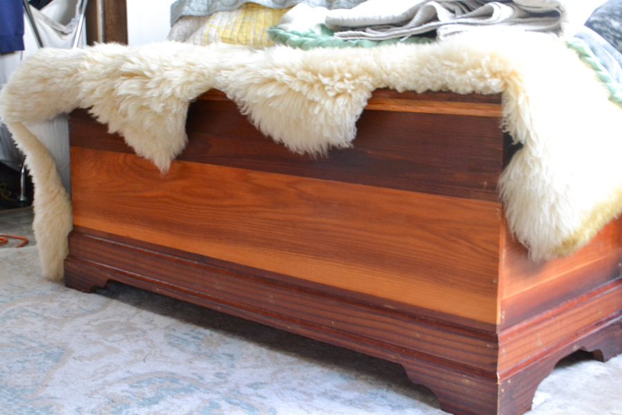A brown cedar hope chest with an off white sheepskin rug on top