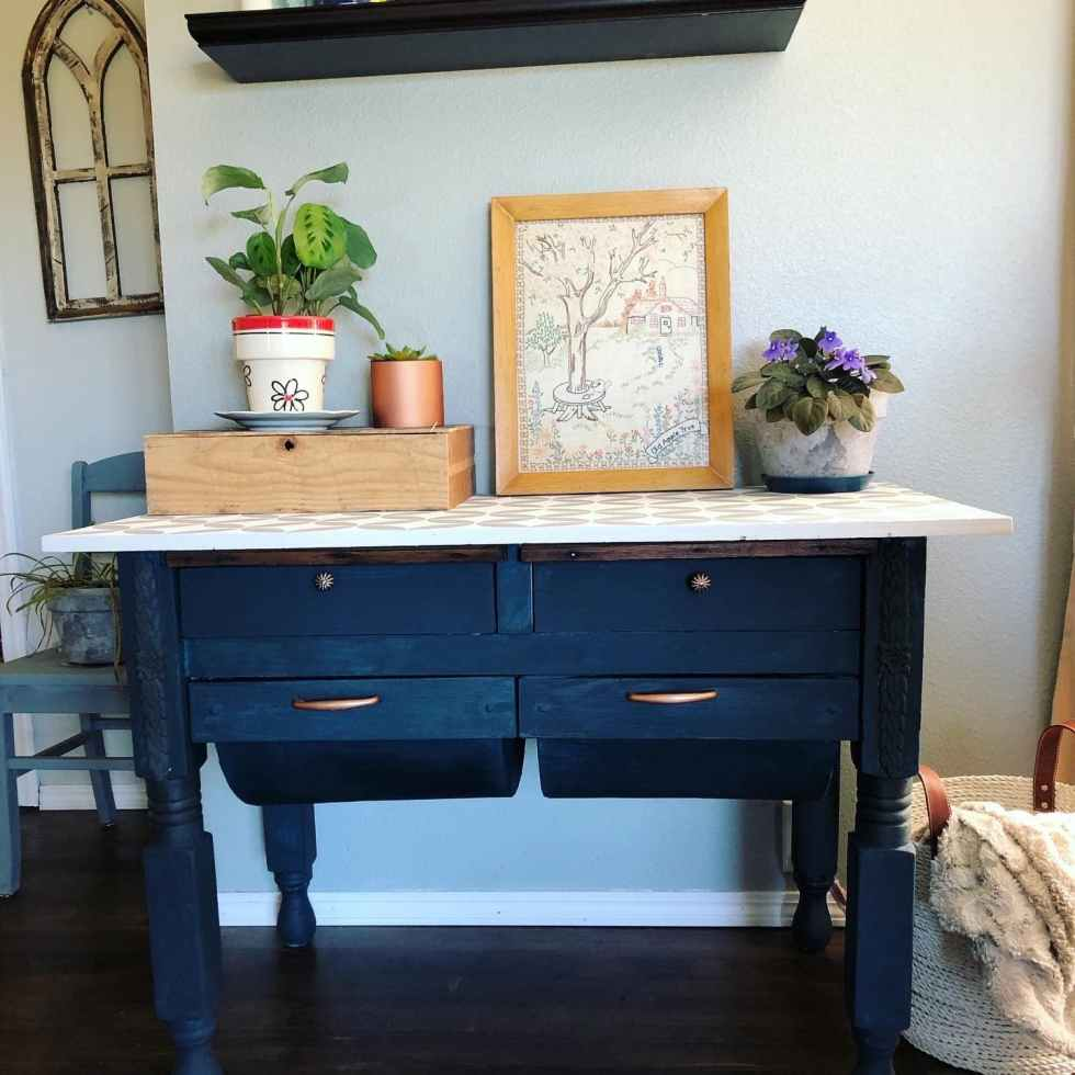 A complete view of a blue painted farmhouse table with drawers and a plant and wood crate sitting on top