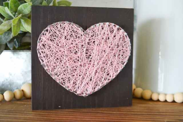 A pink string art heart on a brown wood sitting on a mantel