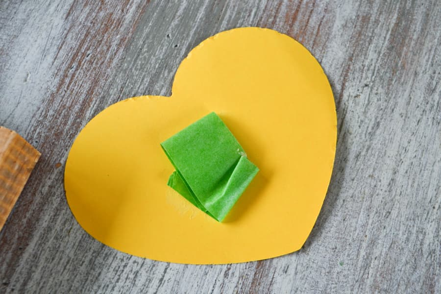 A yellow paper heart with a green piece of painters tape on the back