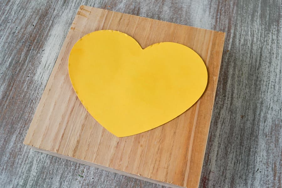 A yellow cardstock heart on top of an unfinshed wood piece